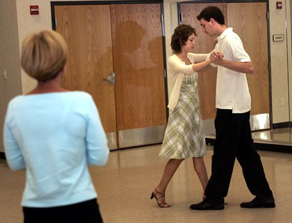 Working under the watchful eye of instructor Sue Flanagan (left), dancers Alone Gorer and Alex Baxter practice their tango steps.