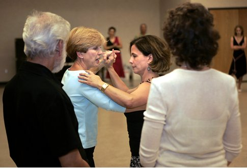 Dance instructor Sue Flanagan (second from left) shows student Barbara Valdez some tango moves as fellow class members look on.