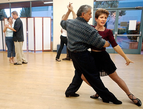 Sue Lindenberg, dance instructor and owner of Tango Fantástico, is led by Bernardo Lucero as she teaches a move during a recent class in Morgan Hill.